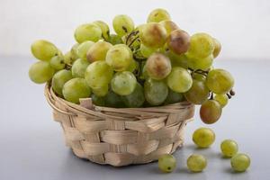 uva bianca in un cesto su sfondo grigio