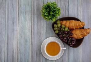 fotografia di cibo piatto laici di una tazza di tè con pane e frutti di bosco con copia spazio foto