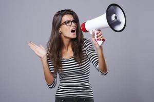 donna che tiene un altoparlante e urla attraverso di esso foto