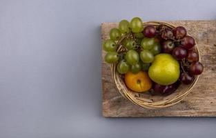 frutta assortita in un cesto su sfondo neutro
