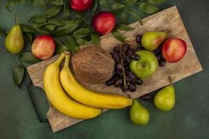 frutta assortita sul tagliere su sfondo verde