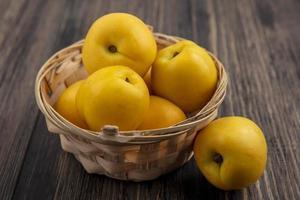 frutta nectacot fresca in un cesto su sfondo di legno