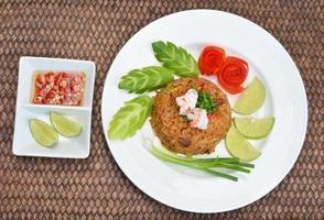 Il riso fritto con gamberetti tailandesi serve sul piatto foto