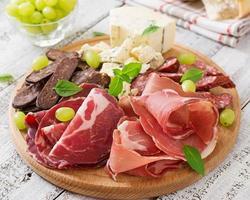 tagliere di antipasti con pancetta, carne secca, salsiccia, formaggio blu foto