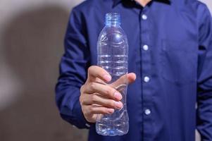 uomo d'affari che tiene una bottiglia di acqua di plastica vuota