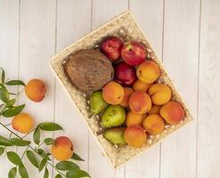 frutta in un cesto con foglie su fondo in legno