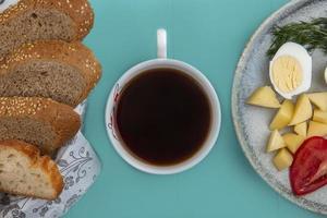 tazza di tè con pane e verdure su sfondo blu foto