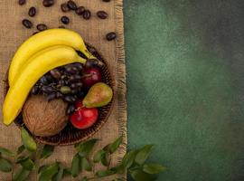 vista dall'alto di frutta in un cesto su tela di sacco e sfondo verde