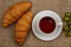 croissant e tè su sfondo di tela di sacco