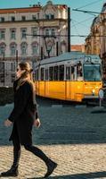 budapest, ungheria, 2020 - donna che cammina davanti a un tram