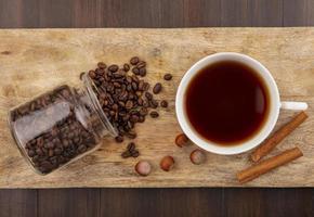 chicchi di caffè e una tazza di tè su fondo in legno foto