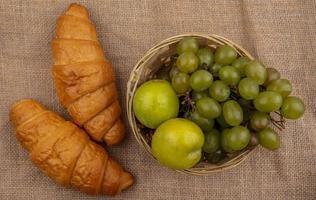 croissant e cesto di uva e pluots su sfondo di tela di sacco