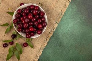 ciliegie in una ciotola ob tela di sacco su sfondo verde