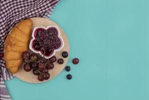 croissant e frutta su panno plaid su sfondo blu