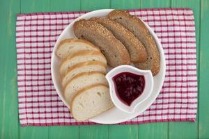 fette di pane con marmellata su panno plaid su sfondo verde foto