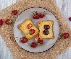 pane tostato e frutta su un piatto su fondo di legno grigio