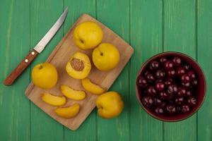 albicocche con coltello e ciliegie su sfondo verde