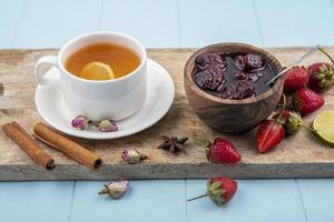 tè e marmellata di frutti di bosco su una tavola di cucina in legno foto