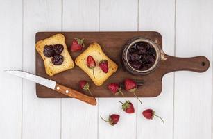 toast con frutti di bosco e marmellata su un fondo di legno bianco foto