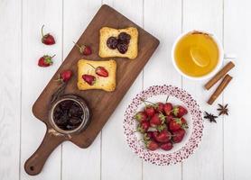toast con frutti di bosco e marmellata su un fondo di legno bianco