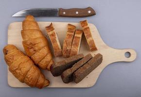 pane a fette sul tagliere e coltello su sfondo grigio