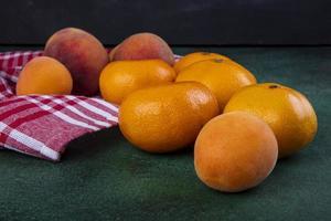 vista laterale di pesche con mandarini foto