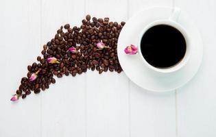 vista dall'alto di una tazza di caffè e chicchi di caffè foto