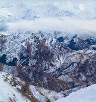 vista a volo d'uccello di montagne marroni coperte di neve