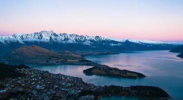 specchio d'acqua con città e montagne al tramonto