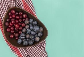 vista dall'alto di deliziose ciliegie rosse con prugnole viola scuro