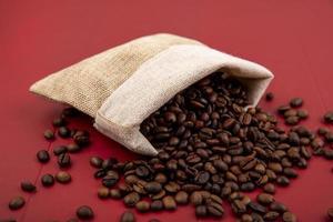 vista dall'alto di chicchi di caffè tostati che cadono da un sacchetto di tela