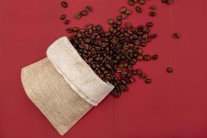 vista dall'alto di chicchi di caffè tostati freschi che cadono da un sacchetto di tela foto