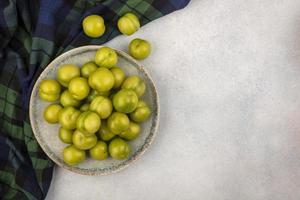 vista dall'alto di prugne verdi nel piatto sul panno plaid e su sfondo bianco con spazio di copia