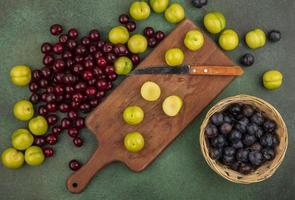 vista dall'alto di prugne ciliegie verdi fresche su una tavola di cucina in legno