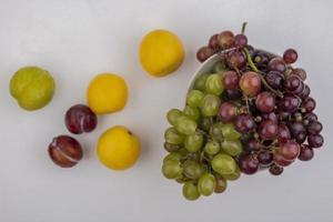vista dall'alto di uva in una ciotola con pluots e nettacots su sfondo bianco