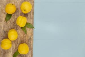vista dall'alto di fresche deliziose pesche gialle isolate su una tavola di cucina in legno su uno sfondo blu con spazio di copia foto