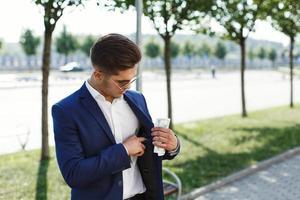 uomo in giacca e cravatta mette i contanti nella tasca interna