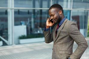 colloqui di uomo d'affari nero afroamericano alla moda sul suo smartphone foto
