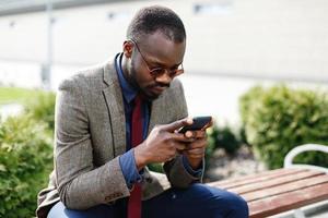 uomo d'affari afroamericano lavora nel suo smartphone seduto sulla panchina all'esterno foto