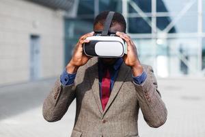 uomo d'affari afroamericano gioca in un vr-occhiali in piedi fuori