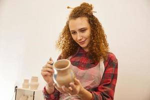 la ragazza abbastanza riccia dipinge un vaso prima della cottura