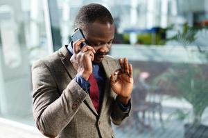 colloqui di uomo d'affari afroamericano alla moda sul suo smartphone foto