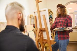 ragazza riccia sta disegnando un ritratto di un uomo