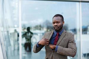 elegante uomo d'affari afroamericano nero prende qualcosa dalla sua tasca foto