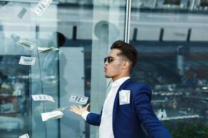 i dollari volano intorno al bel giovane uomo d'affari