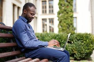 felice uomo afroamericano lavora sul suo computer portatile foto