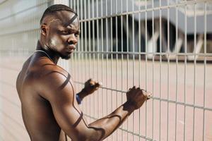 uomo nero muscoloso dalla recinzione