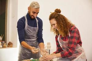 l'uomo e la ragazza stanno modellando un vaso e sorridendo foto
