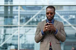 elegante uomo d'affari afroamericano nero lavora sul suo smartphone foto