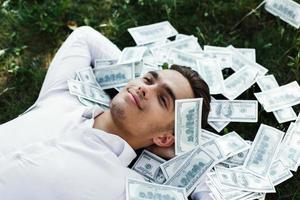 uomo sdraiato sull'erba con banconote da cento dollari